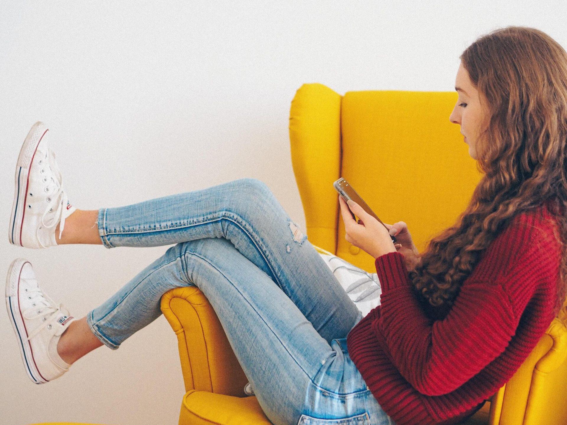 mujer sentada en una silla en el teléfono